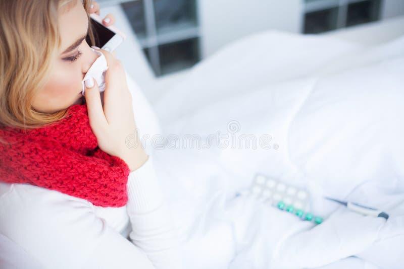 冷流感 病的妇女在床上在家谈话在电话 免版税库存照片