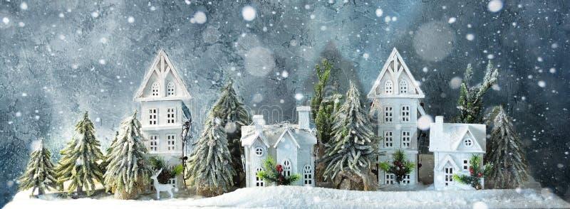 冷淡的有降雪、房子和树的冬天久的横幅妙境森林 背景圣诞节概念问候查出白色 库存图片