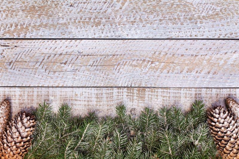 冷淡的杉木分支和锥体在被风化的白色木桌上- 免版税库存照片