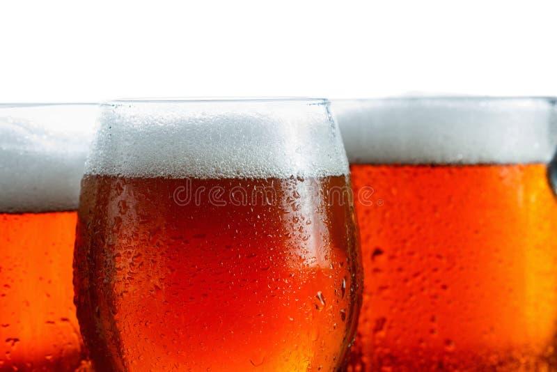 冷淡的杯凉快的啤酒起泡沫,用下落盖,特写镜头 查出在白色 免版税库存图片