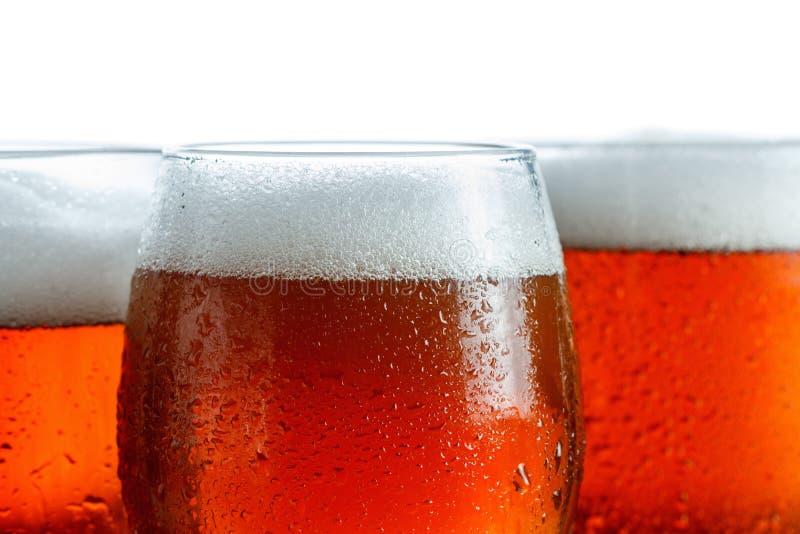 冷淡的杯凉快的啤酒起泡沫,用下落盖,特写镜头 查出在白色 图库摄影