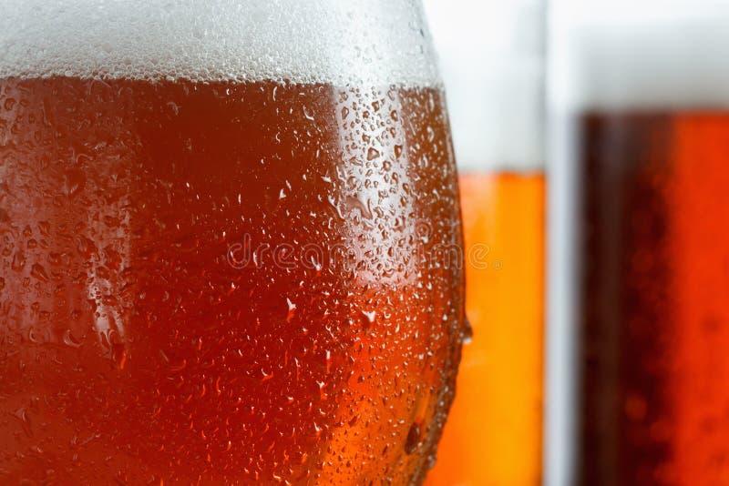 冷淡的杯凉快的啤酒起泡沫,用下落盖,特写镜头 免版税库存图片