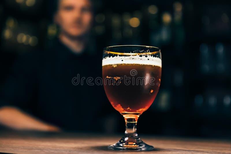 冷淡的杯在酒吧柜台的低度黄啤酒 杯在一间黑暗的客栈的啤酒 侍酒者是在背景 库存图片