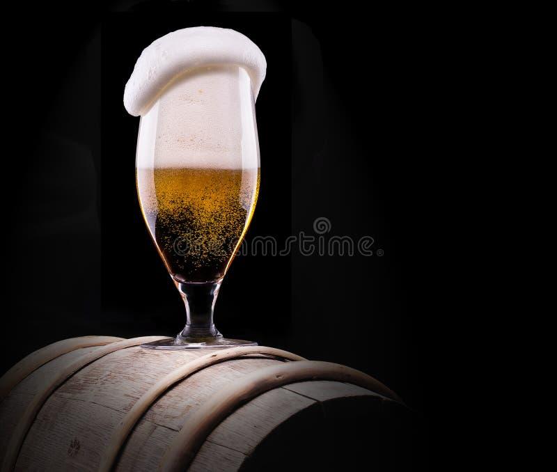 冷淡的杯在黑背景的低度黄啤酒 库存图片