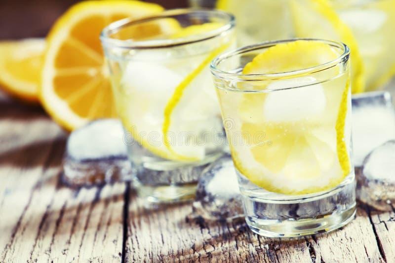 冷的俄国伏特加酒用柠檬和冰在小玻璃,葡萄酒求爱 免版税库存照片