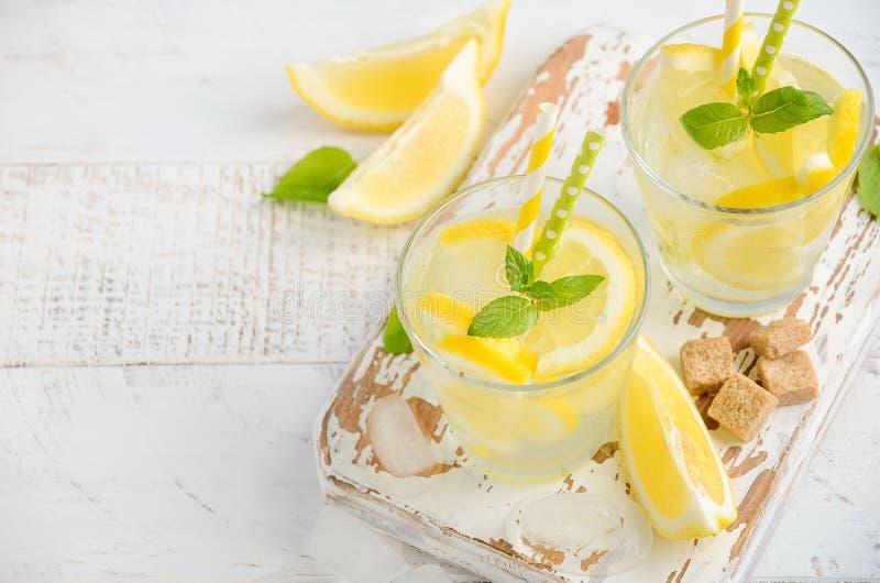 冷的刷新的夏天饮料用柠檬和薄菏在木背景 免版税库存图片