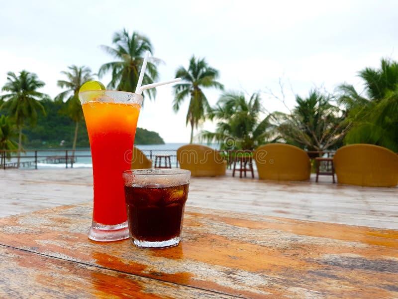 冷的可乐和柠檬茶的两杯在海海滩背景 免版税库存照片