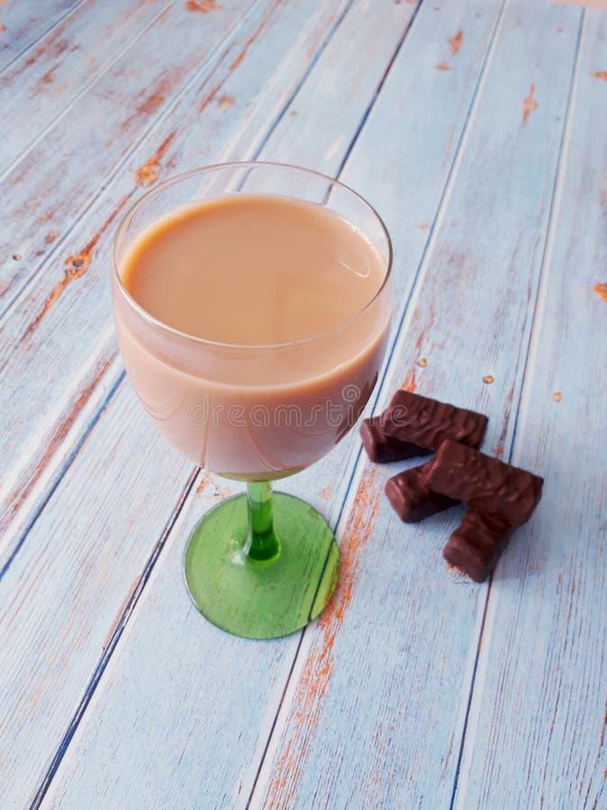 冷的咖啡用在一个玻璃觚和巧克力的牛奶在一张木桌上 免版税库存图片