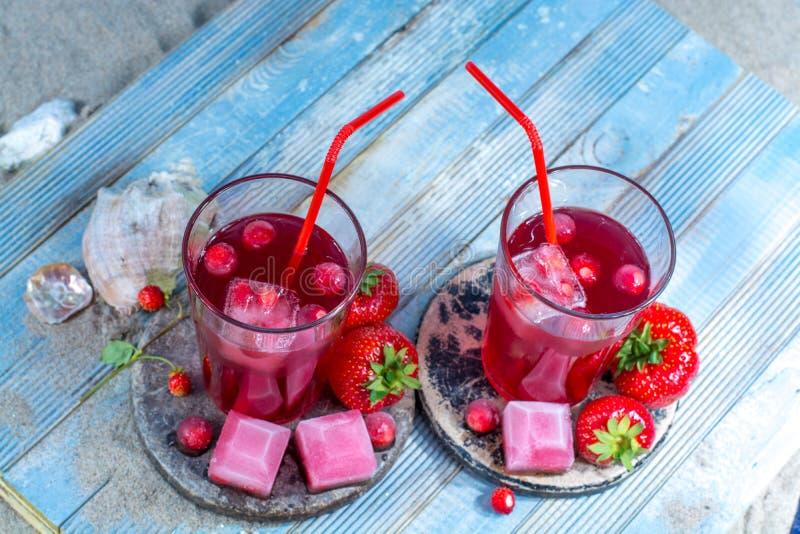 冷的新鲜的桃红色果汁饮料在与贝壳的沙滩服务 免版税库存照片