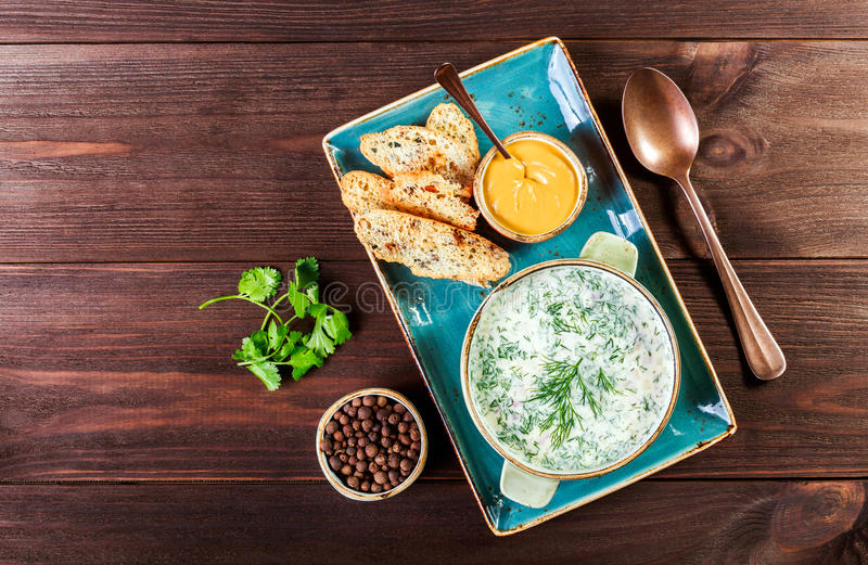 冷的汤或夏天酸奶用萝卜、黄瓜、莳萝、草本和薄脆饼干在黑暗的木背景 Okroshka 是可能食物自创饼 库存图片