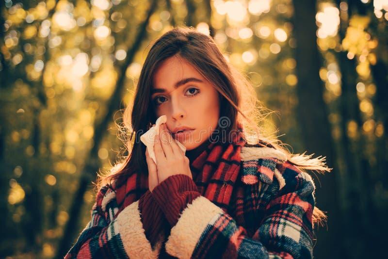 冷的流感季节流鼻水 有过敏症状吹的鼻子的妇女 嗅鼻孔喷射的少妇画象 免版税图库摄影