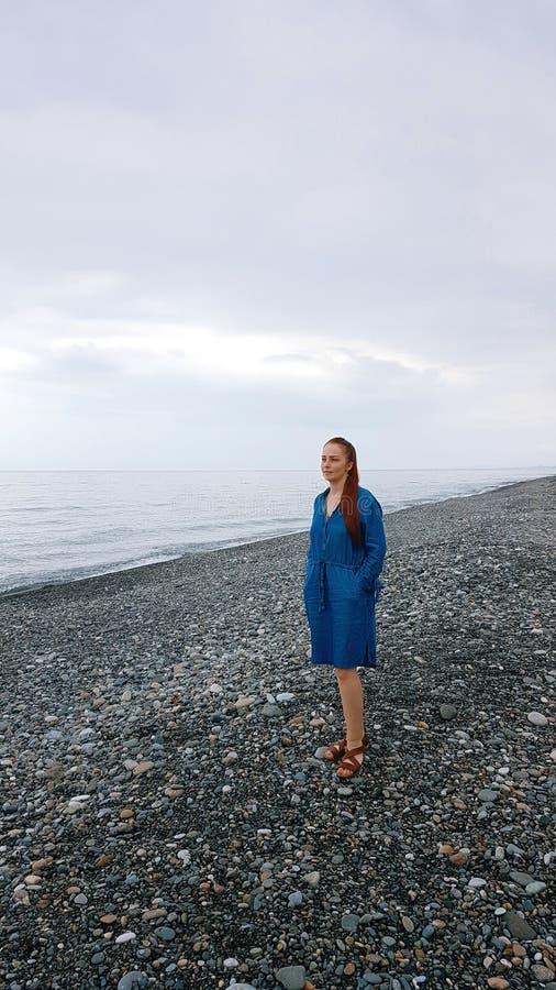 冷的海的岸的妇女在一阴天 免版税图库摄影