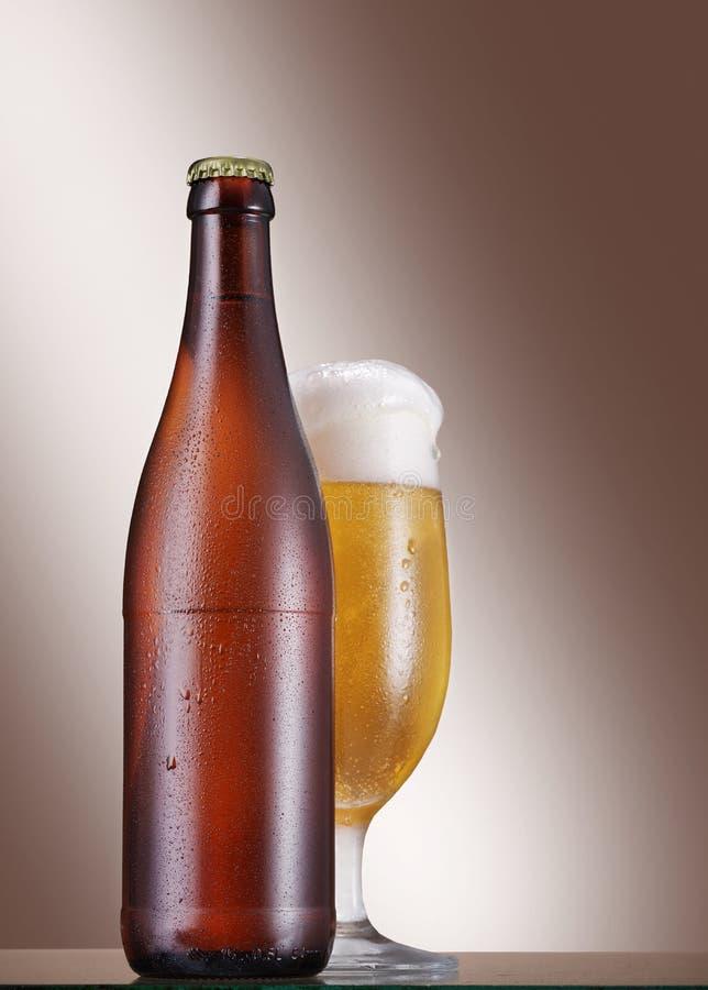 冷的瓶和杯在桌上的啤酒在米黄背景 图库摄影