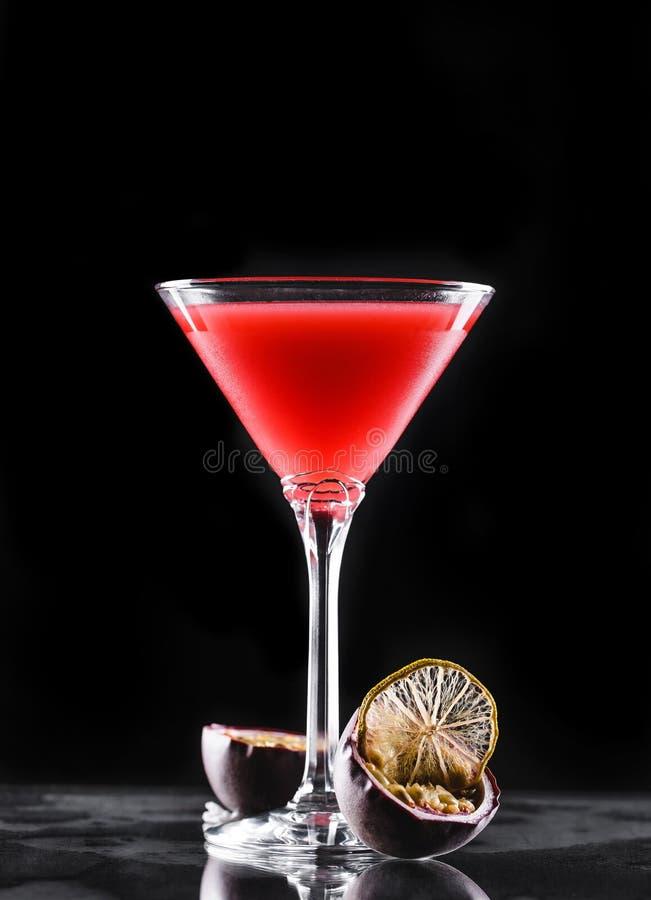 冷的红色鸡尾酒用在高玻璃的西番莲果在黑背景 夏天饮料和酒精鸡尾酒 免版税库存图片