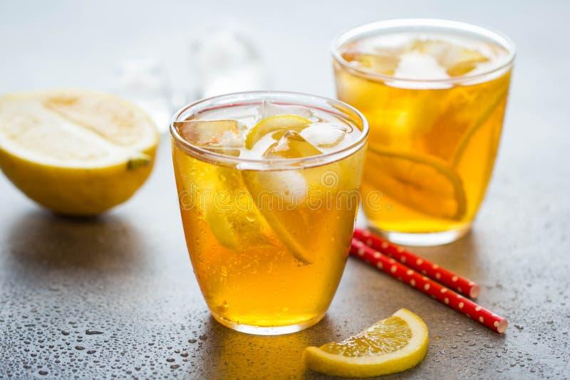 冷的茶用柠檬和冰在一块玻璃与下落,新鲜的甜果汁饮料,夏天生气勃勃,可口柠檬水 免版税库存照片