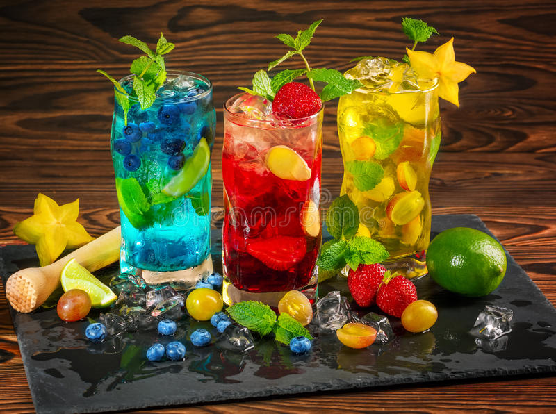 冷的蓝色和黄色mojitos 红色mojito用薄菏 Mojito用兰姆酒 在木背景的酒精 夏天饮料和鸡尾酒 免版税库存照片