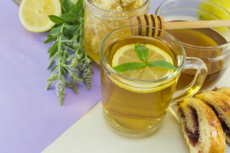冷的薄荷的茶用在一张桌上的柠檬与薄荷的植物,蜂蜜, dippe 免版税库存照片
