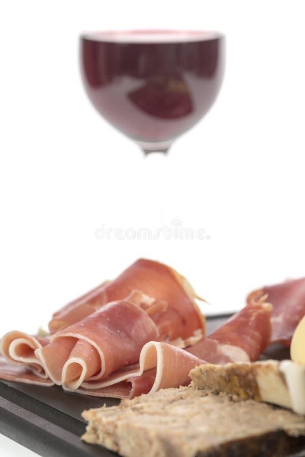 冷盘和乳酪的选择在一个盛肉盘有一杯的红葡萄酒 免版税库存照片