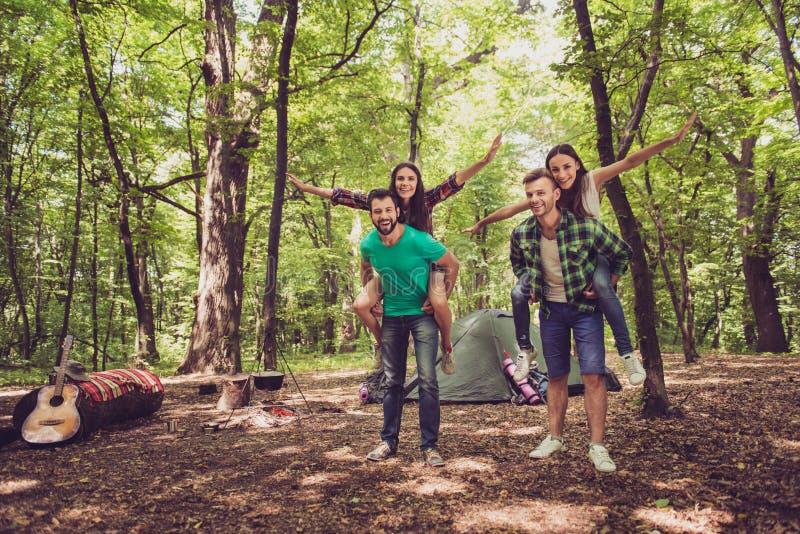 冷颤、乐趣、喜悦、爱和友谊!四个朋友在木头无所事事在营地,男孩扛在肩上他们的夫人 豆杆 库存图片