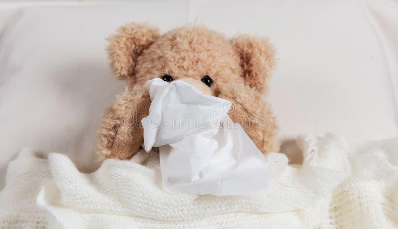 冷,通气管或者过敏 逗人喜爱的女用连杉衬裤在床上,盖用一条温暖的毯子,拿着组织 库存照片