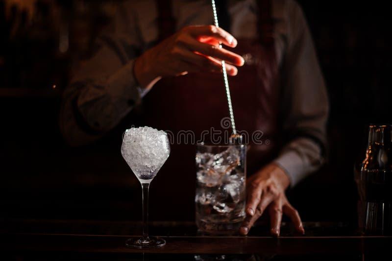 冷却与匙子的侍酒者鸡尾酒杯混合的冰 免版税库存图片