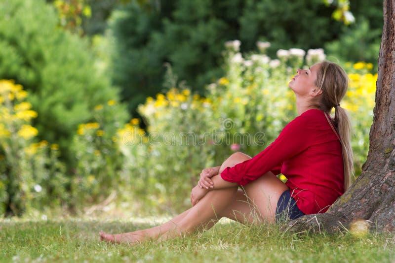 冷却享受夏天生气勃勃的少妇在树下 免版税图库摄影