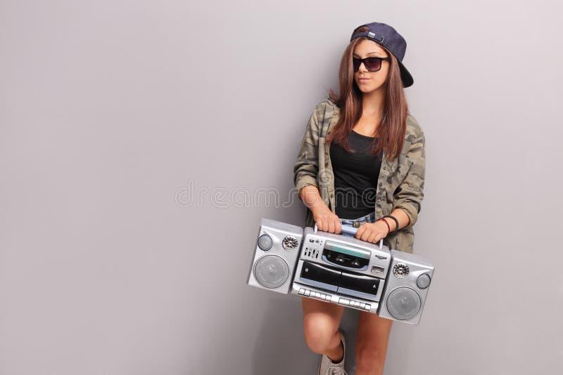 冷却拿着收音机的Hip Hop成套装备的十几岁的女孩 免版税图库摄影