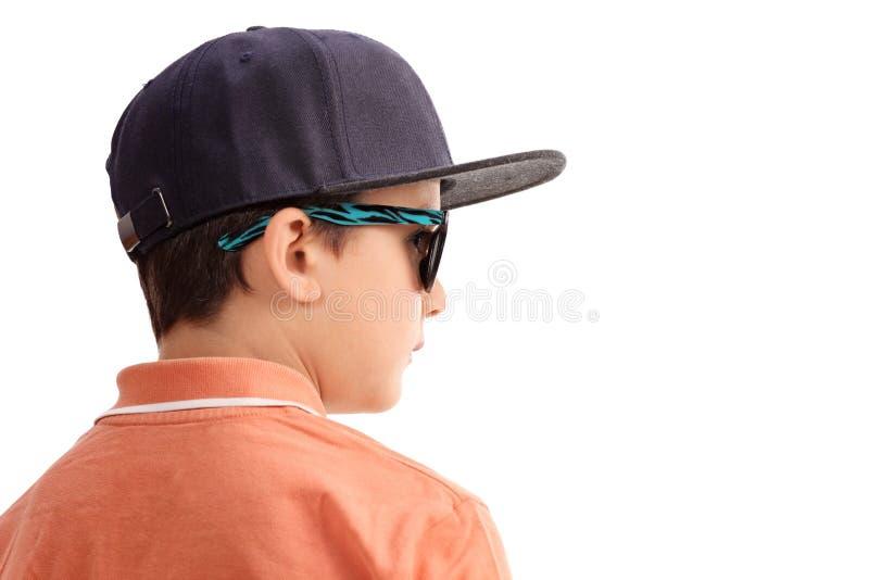 冷却有盖帽和太阳镜的小男孩 免版税图库摄影