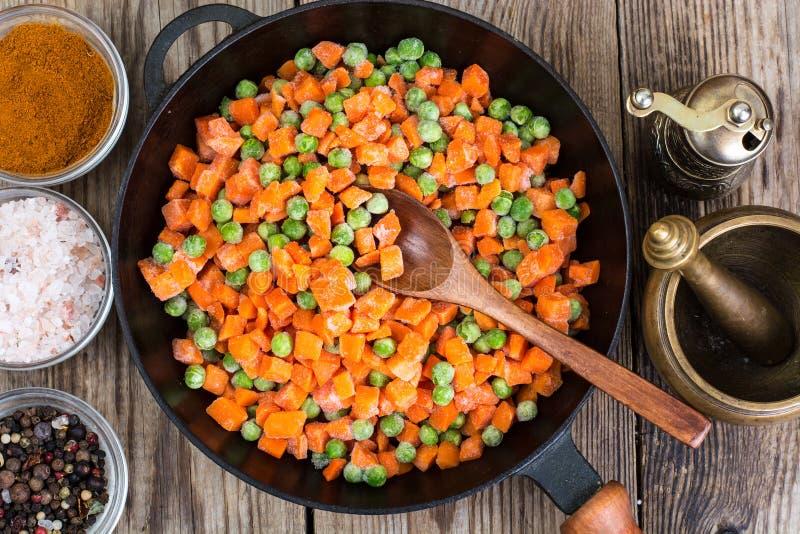冷冻豌豆和红萝卜烹调的在平底锅 库存图片
