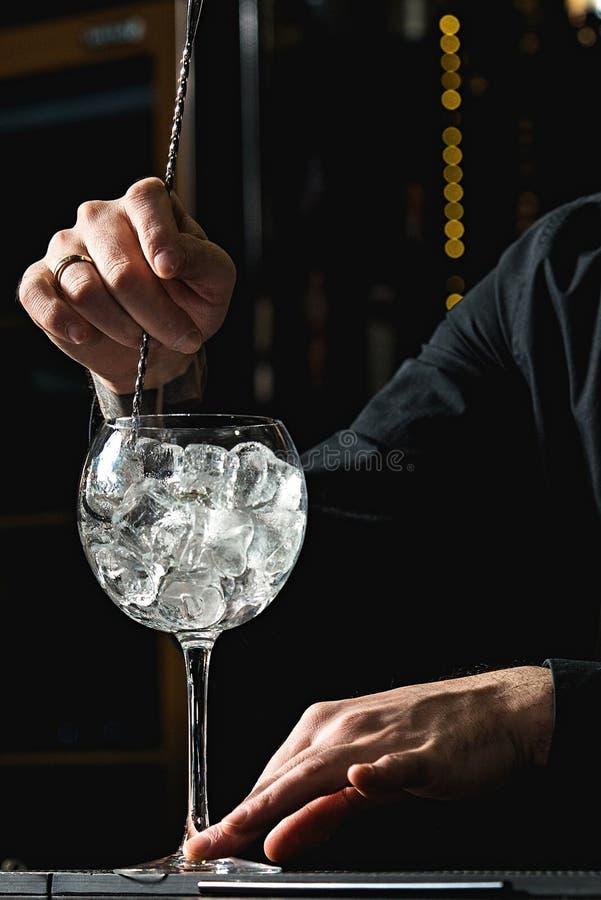 冷却鸡尾酒杯的侍酒者 免版税库存图片