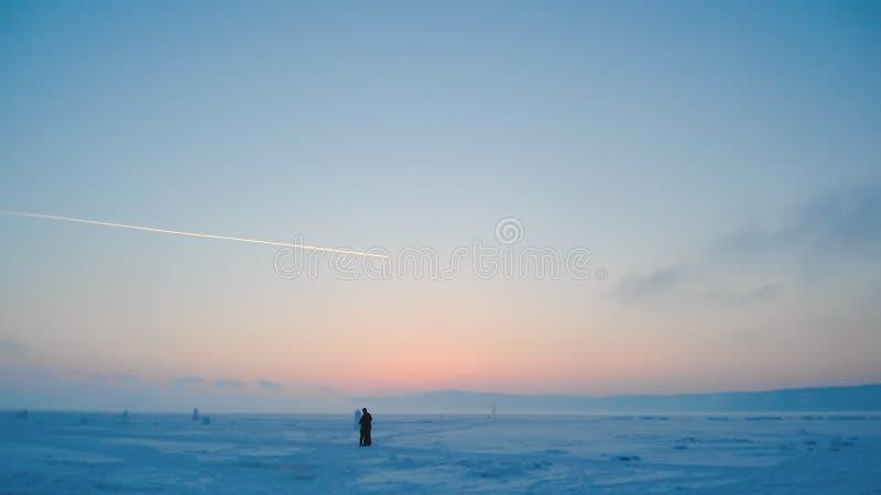 冻湖多雪的平原看法日落的 免版税库存图片