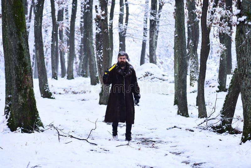 冻结的住在森林并熟悉森林的人概念 皮大衣的人走在森林里的 免版税图库摄影