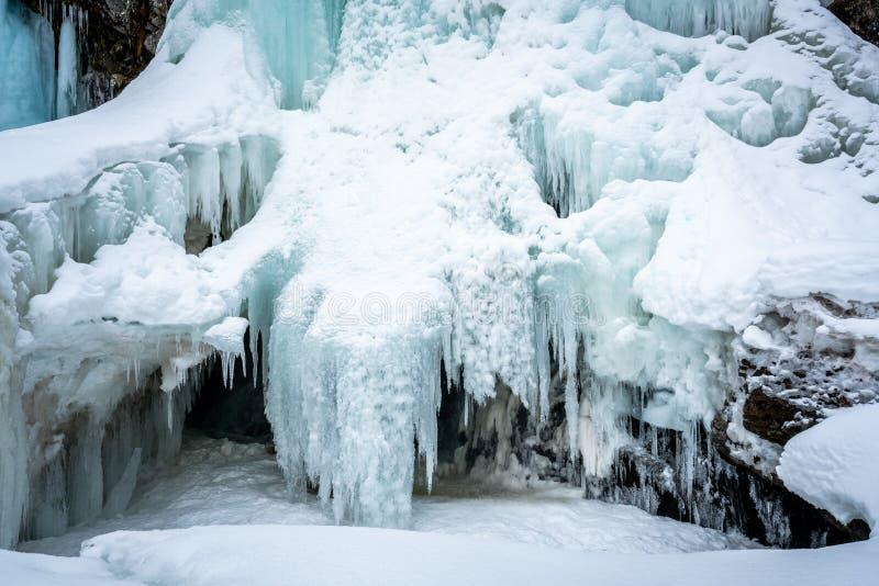 冻结的冬天北极瀑布 与白雪的蓝色冰层 免版税库存照片