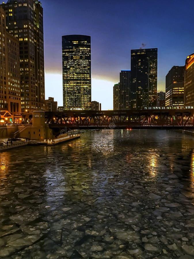 冻芝加哥河看法和当el火车通过在晚上与冰大块的高峰时间在河 免版税库存图片