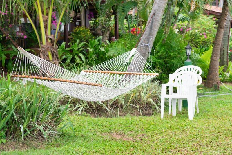 净吊床在棕榈树垂悬了在一家热带旅馆里 库存照片