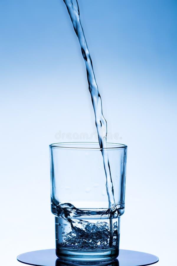净水涌入在白蓝色背景的一个玻璃烧杯 图库摄影