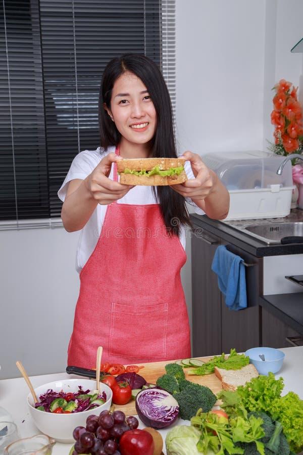 准备一个三明治的妇女在厨房屋子里 免版税库存图片