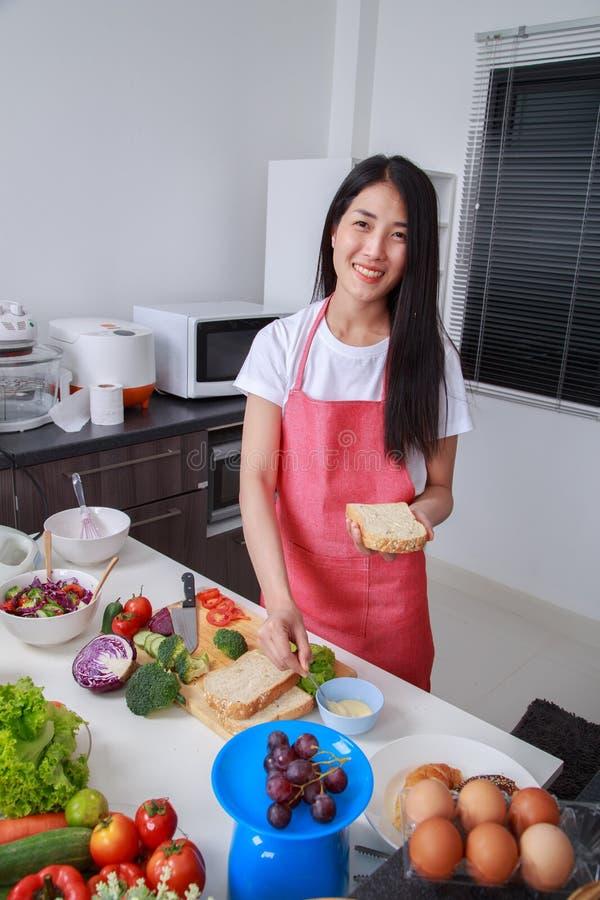 准备一个三明治的妇女在厨房屋子里 库存照片