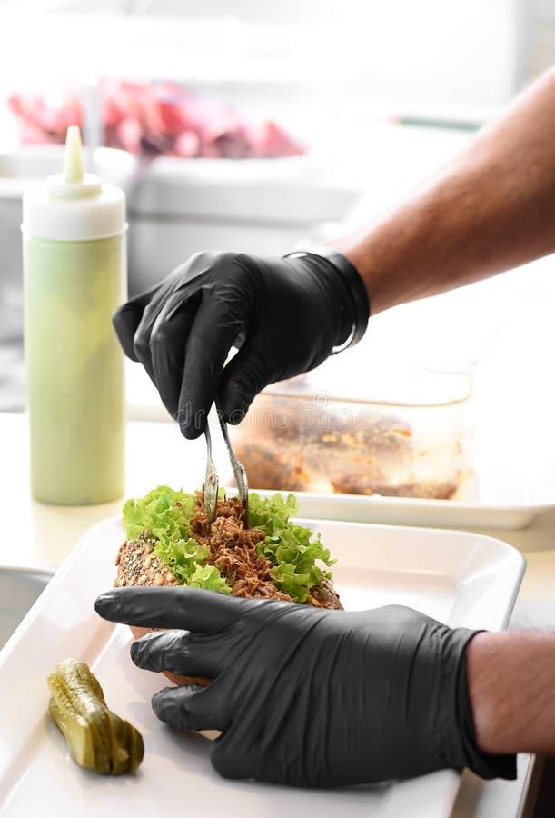 准备一个被拉扯的猪肉三明治的厨师 免版税库存图片