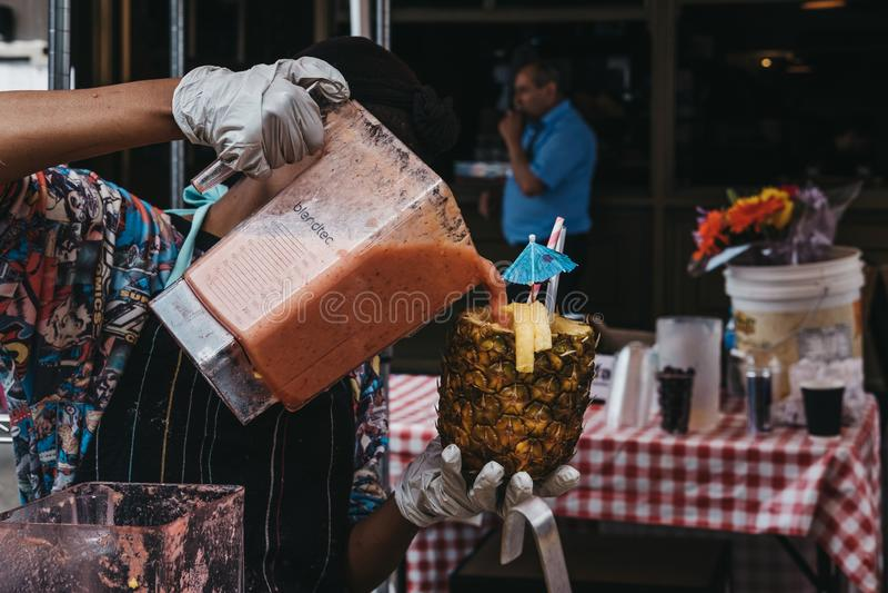 准备一份热带饮料的妇女在市场摊位在波托贝洛 免版税库存图片