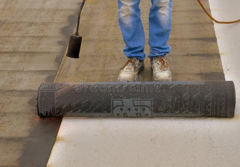 准备一部分的沥清屋顶毛毡卷的工作者 免版税库存照片