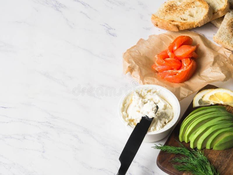 准备三明治的成份与奶油奶酪,三文鱼,在烤多士的鲕梨在白色大理石背景 复制空间 库存照片