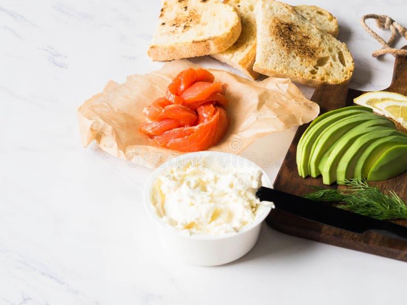 准备三明治的成份与奶油奶酪,三文鱼,在烤多士的鲕梨在白色大理石背景 复制空间 免版税库存照片