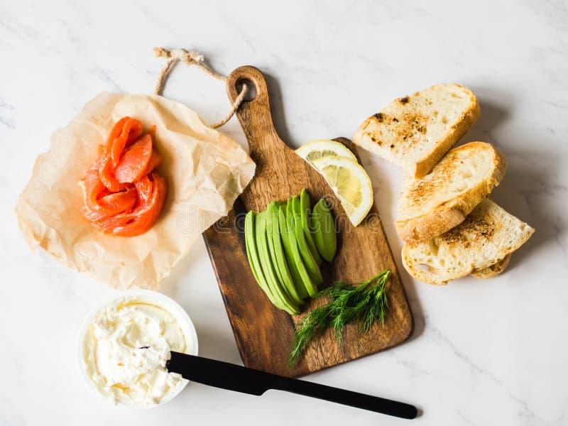 准备三明治的成份与奶油奶酪,三文鱼,在烤多士的鲕梨在白色大理石背景 顶视图 免版税库存图片