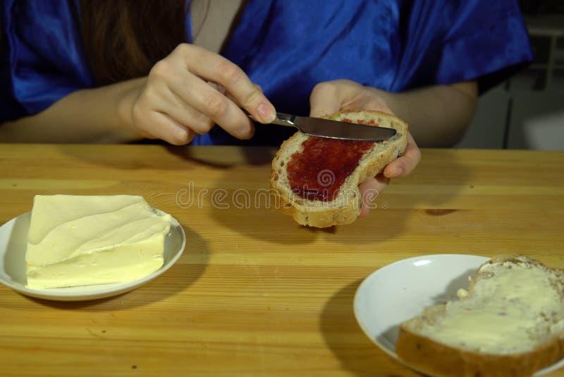 准备三明治,在面包的传播红色果酱的少妇 免版税库存图片