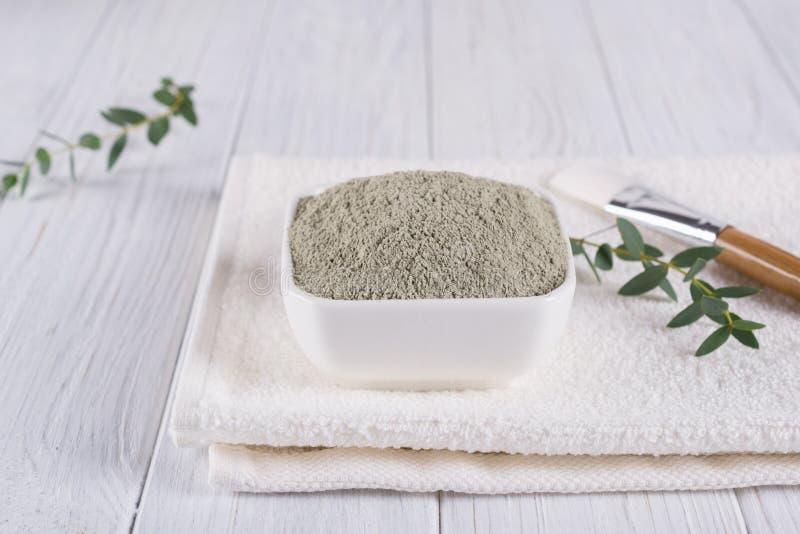准备与各种各样的skincare产品的化妆泥面具 在碗的干燥黏土粉末 家或沙龙温泉款待的自然化妆用品 库存图片