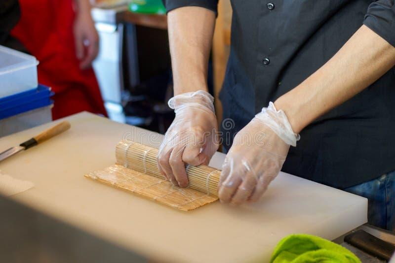 准备与竹席子的日本厨师寿司卷 免版税图库摄影