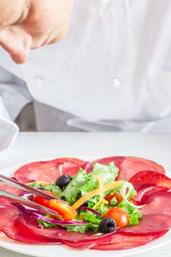 准备与bersaola和凉拌生菜的厨师盘 库存照片