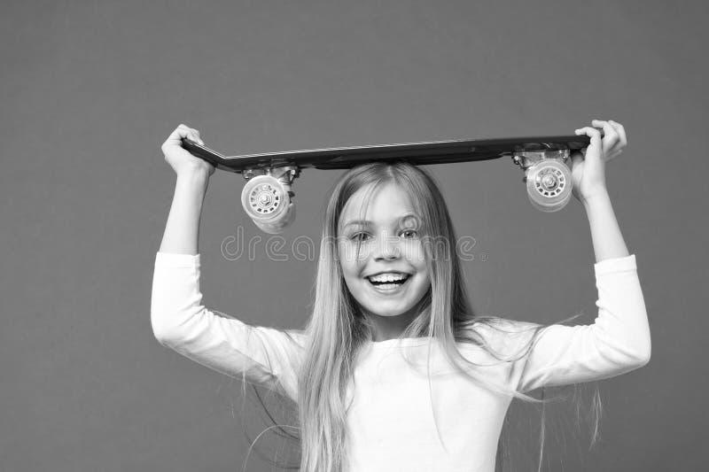 准备乘驾 溜冰板运动是乐趣 紫罗兰色背景的愉快的溜冰者女孩 童年发展和幸福 免版税库存照片
