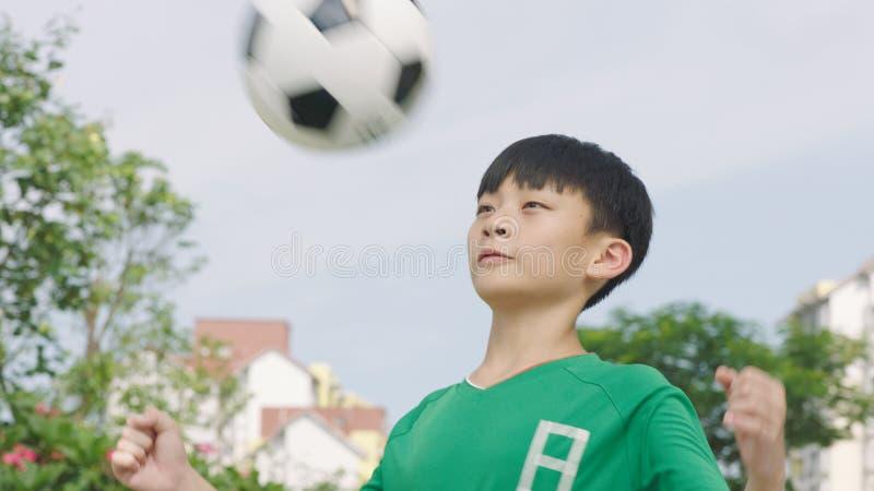 准备亚裔少年的足球运动员停止与胸口的球户外 免版税图库摄影
